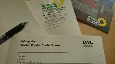 """Bild: Blatt mit Überschrift """"Anfrage"""", Stift und Teil der Broschüre mit Logo der GRÜNEN"""